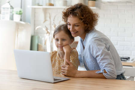 Virtual shopping. Smiling single mom help child junior girl choose school supplies at online web store. Bonding adult mother and daughter kid sit by kitchen table watch funny video in app on laptop pc