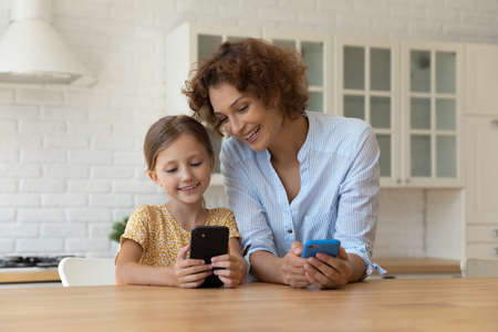 Catch it. Young grown mother little child daughter two skilled users hold phones share photo video files by wifi. Friendly adult elder younger sisters exchange data in virtual space using cell devices