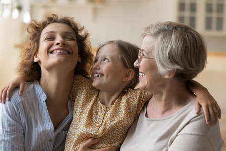 3 generations women. Overjoyed happy little girl embrace shoulders of laughing mother smiling older grandmother. Loving family of three diverse age females spend time together hug on sofa having fun