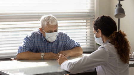 Close up female doctor consulting smiling older patient wearing medical face mask about health insurance agreement at meeting in hospital, therapist and elderly patient discussing contract terms Stock fotó