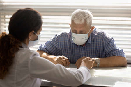 Close up female therapist consulting mature man patient wearing medical face mask about health insurance agreement, contract terms, discussing checkup results, prescriptions, healthcare concept
