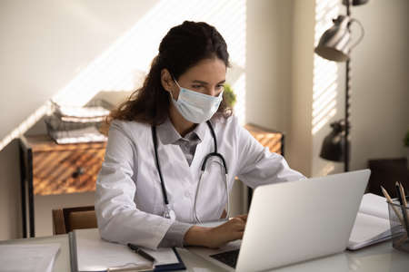 Close up focused professional female doctor physician wearing protective face mask using laptop, looking at screen, consulting patient online, chatting, browsing medical apps, searching information Foto de archivo