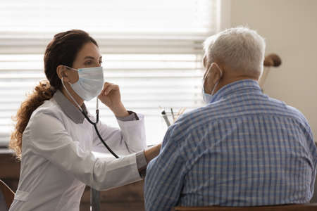 Confident female doctor wearing face mask checking mature man lungs, using stethoscope, listening to elderly patient heartbeat, breath, elderly generation healthcare, medical checkup concept