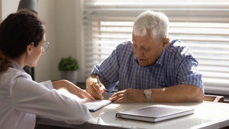 Close up mature man signing contract in doctor office, female therapist physician pointing finger at document, senior patient making health insurance deal, putting signature, healthcare concept