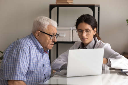 Close up female professional doctor consulting mature patient wearing glasses, using laptop, demonstrating medical checkup result, explaining prescription, treatment, healthcare service concept Stock fotó