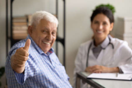 Close up focus on hand mature patient showing thumb up, female therapist and senior man sitting in office, happy old client satisfied by health insurance service, good healthcare concept
