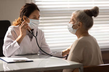 Close up female doctor wearing face mask checking mature patient lungs, holding using stethoscope, listening to elderly woman breath, sitting in hospital office, medical checkup and healthcare Standard-Bild