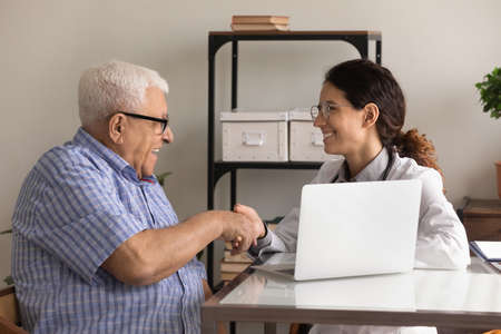 Smiling female doctor and mature man wearing glasses shaking hands, greeting, sitting at table in hospital, older patient making health insurance deal, agreement, good medical checkup result