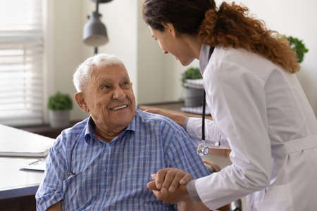 Close up caring nurse holding smiling mature patient hand at meeting in hospital, doctor caregiver wearing uniform comforting and supporting senior man, good news about treatment, empathy and care Stock fotó