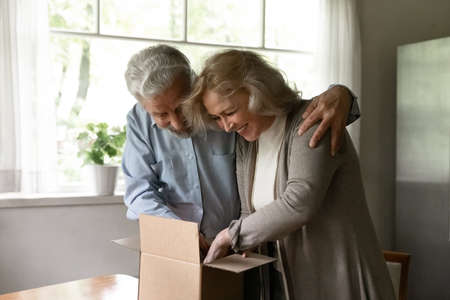 Happy excited retired family couple unpacking parcel at home. Middle aged man and woman receiving package from online purchase delivery service, opening cardboard box together, smiling and laughing Stock Photo