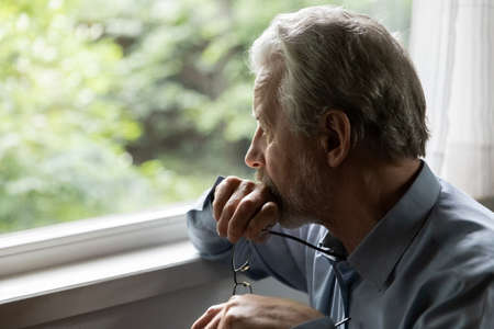 Pensive mature 70s aged man in deep thoughts holds glasses, looks out window. Thoughtful older person feels concern, depressed elder thinks of health problem and loneliness, suffers from memory loss Foto de archivo