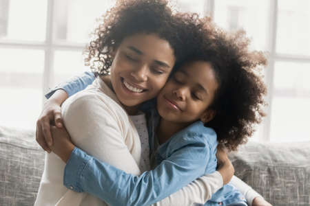 Portrait of happy mum with shut eyes embracing daughter girl. Affectionate Black mother and kid expressing love, hugging, spending good time together at home. Family, affection concept. Close up Stock Photo