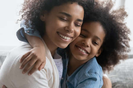 Happy African American girl embracing her peaceful mum with closed eyes. Mother enjoying leisure time with her daughter kid at home, hugging child and cuddling child. Family bonding, love concept Stock Photo - 164758784