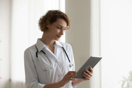 Young Caucasian female doctor in white medical uniform hold tablet talk speak on video call with hospital patient. Woman GP use pad gadget have webcam online consultation. Virtual event concept.