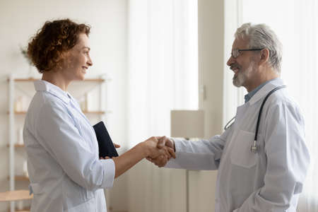 Smiling diverse doctors in white medical uniforms shake hands get acquainted in hospital. Happy colleagues handshake greeting or close deal in clinic. Medicine, healthcare, acquaintance concept.