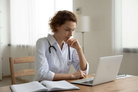 Pensive female doctor sit at desk in hospital work online on computer thinking pondering of solution. Thoughtful woman GP look at laptop screen consult patient on webcam. Technology concept.