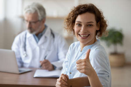 Overjoyed young Caucasian female patient show thumb up satisfied with consultation with doctor. Smiling woman client satisfied recommend good quality service in hospital. Recommendation concept.