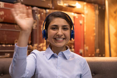 Head shot portrait smiling Indian woman wearing headphones waving hand at camera, businesswoman involved in internet meeting, video call, greeting viewers, happy mentor teacher leading online lesson