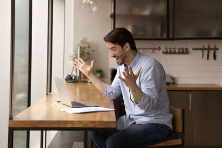 Overjoyed surprised businessman wearing glasses rejoicing success, business achievement, looking at laptop screen, young man reading unbelievable good news, received job promotion, money refund