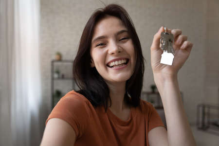 Starting new life. Overjoyed young female hold keys from new home look at camera shoot selfie portrait to share news at social network. Excited millennial lady proud of becoming homeowner first time Stock fotó
