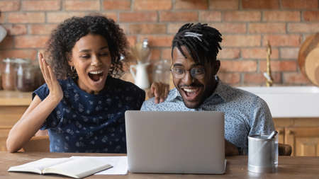 Unbelievable. Amazed millennial black spouses get super offer from web store. Emotional young african couple work with papers at home office online feel excited receive loan mortgage approval by email