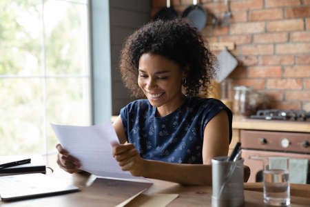 Joyful young mixed race female open paper written letter happy to read positive news from friend. Satisfied self employed black businesswoman get official answer about receiving credit loan from bank Banque d'images
