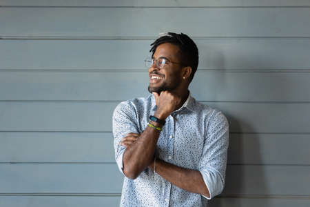 Bearded dreamer. Smiling millennial afro american man hipster in stylish glasses posing against grey wall look away. Confident motivated young black guy dream think feel hopeful optimistic. Copy space Foto de archivo
