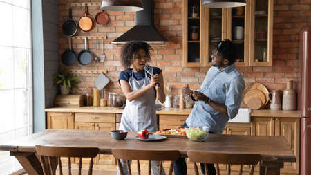 Sing along to my song dear. Joyful millennial black married couple having fun at kitchen sing aloud play music instruments made of kitchenware. Active young black spouses fond of cooking food together