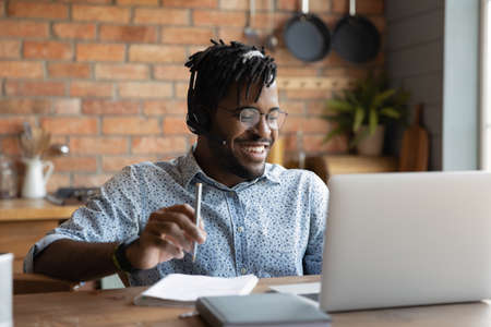 That is funny. Laughing young african guy distance course student in earphones have fun enjoy good joke of teacher on laptop screen. Happy black man trainee get tutor praise for prompt correct answer