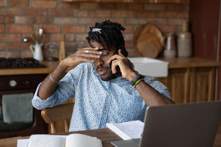 Brain is fried. Exhausted nervous young african male work study from home sit by laptop do paperwork speak on phone. Tired black man student freelancer engaged in multitask feel information overload