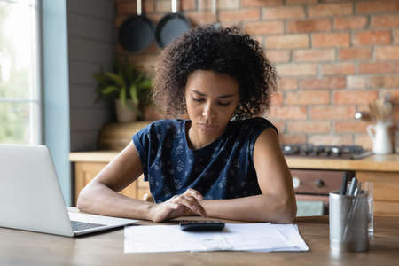Serious mixed race female calculate utility charges check payments sum by loan contract to avoid scam. Thoughtful young black woman engaged in planning monthly budget count tax rate before pay online