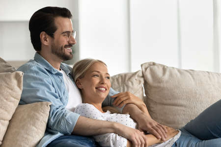 Happy young couple lying relaxing on couch look in distance dreaming thinking of happy future together. Smiling Caucasian man and woman rest on sofa at home, imagine visualize opportunities.