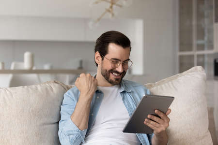 Overjoyed young Caucasian man look at tablet triumph get pleasant good email or message online. Happy millennial male use pad device feel euphoric with lottery win on internet. Success concept. Stock fotó