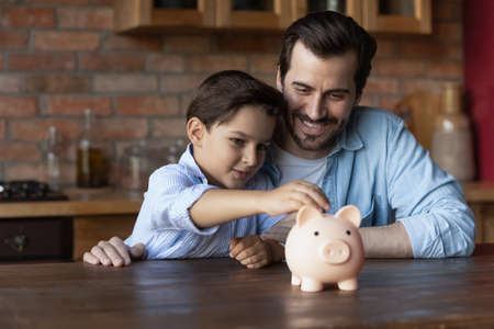 Smiling young Caucasian dad and little 7s son manage family budget put coin into piggybank save money for future needs. Happy smart father and small boy child make financial investment. Bank concept.