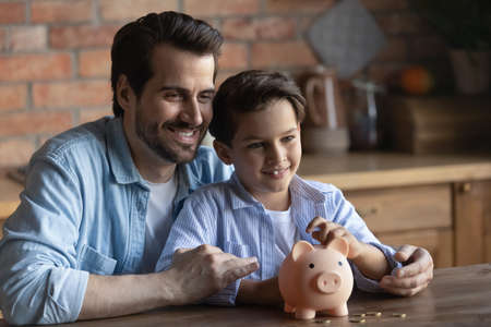Smiling young Caucasian father teach little son saving money managing family budget. Happy 30s dad and small boy child use piggybank collect coins, make investment for future. Finances concept.
