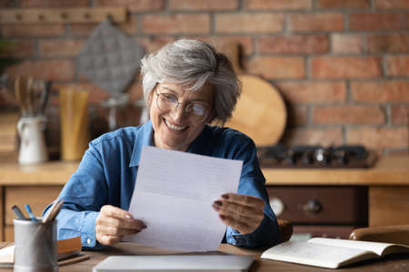 Happy retired hispanic woman bank client hold official document notification informing loan mortgage is paid. Glad smiling aged latin lady read paper letter received by mail satisfied with good news