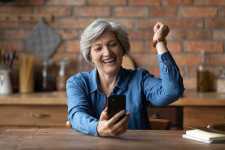 Overjoyed aged senior latin grandmother pensioner yell yes super celebrate winning mobile phone game. Happy elderly female sit at kitchen table read email excited with great sale discount at web shop