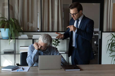 Angry young Caucasian male boss or CEO lecture scold middle-aged employee at workplace. Mad 30s businessman have fight quarrel with senior worker, correct mistakes errors. Discrimination concept.