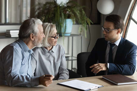 Male bank specialist worker consult mature man and woman spouses about elderly health insurance. Middle-aged Caucasian couple clients customers have meeting with real estate agent or broker.