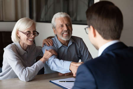 Smiling older Caucasian man and woman clients shake hand greeting get acquainted at meeting with specialist. Happy mature couple customers handshake close deal with real estate agent or broker.