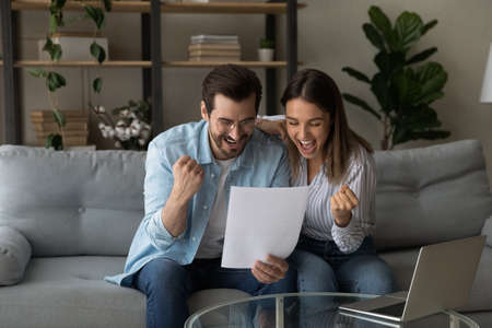 Overjoyed young couple reading good news in letter together, excited wife and husband celebrating success, showing yes gesture, approved loan or mortgage, money refund, sitting on couch at home