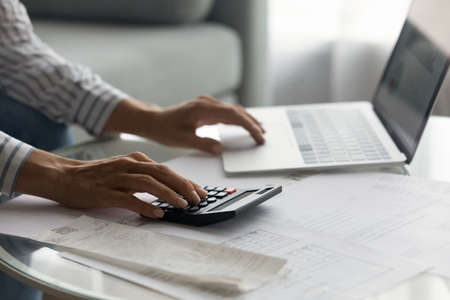 Close up woman using laptop and calculator, planning managing budget, businesswoman calculating bills, expenses, browsing online banking service, sitting at table with financial documents and receipt Foto de archivo