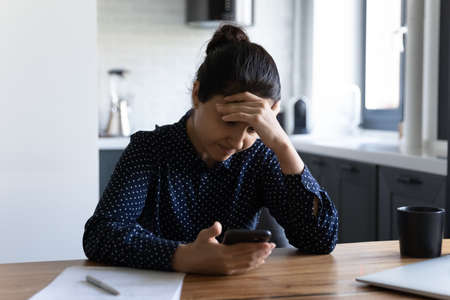 Close up unhappy Indian woman touching forehead, holding phone, reading bad news, unexpected debt or dismiss notification, depressed young female looking at smartphone screen, worried about problems