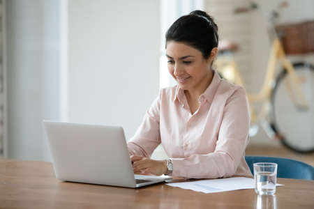 Smiling young Indian female employee sit at desk at workplace look at laptop screen consult client online. Happy mixed race woman work distant on computer with paperwork in office. Technology concept.