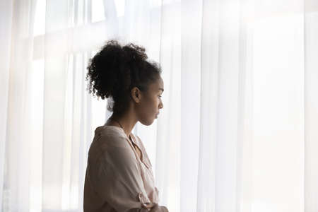 Pensive upset young African American woman look in window distance thinking or pondering. Thoughtful millennial biracial female outcast feel lonely troubled at home. Loner, solitude concept. Stock Photo
