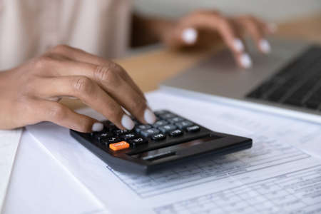 Crop close up of biracial woman calculate expenses expenditures on calculator machine, pay bills taxes online on computer. African American female manage budget on laptop. Saving, finance concept.