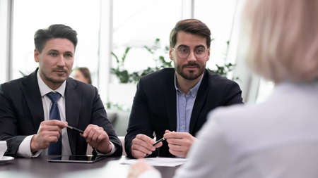 Pensive confident businessmen talk speak with business partner or client at meeting in office. Successful young Caucasian male employers have interview with job candidate. HR, employment concept.