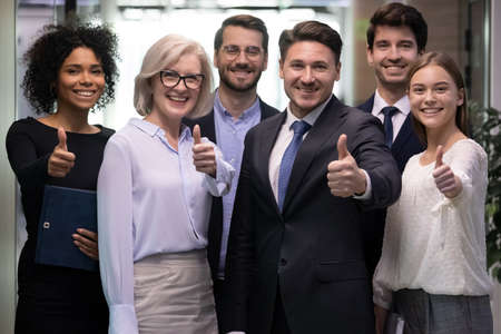 Portrait of smiling multiethnic team show thumbs up give recommendation to good quality service. Happy diverse multiracial businesspeople recommend company or bank experience. Employment concept.