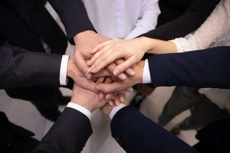 Crop close up top view of multiracial employees colleagues stack hands in pile show team loyalty and unity. Diverse multiethnic businesspeople engaged in teambuilding activity. Teamwork concept. Imagens