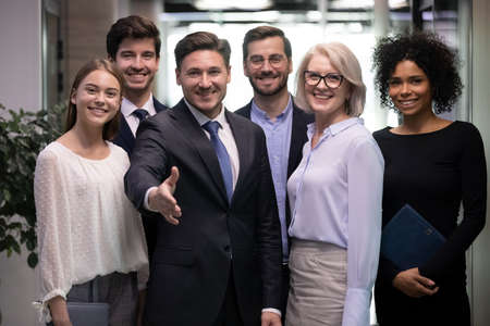 Smiling male CEO or director pose with office team stretch hand get acquainted greet with new employee. Happy businessman meet welcome newcomer newbie at workplace. Recruitment, acquaintance concept. Stockfoto